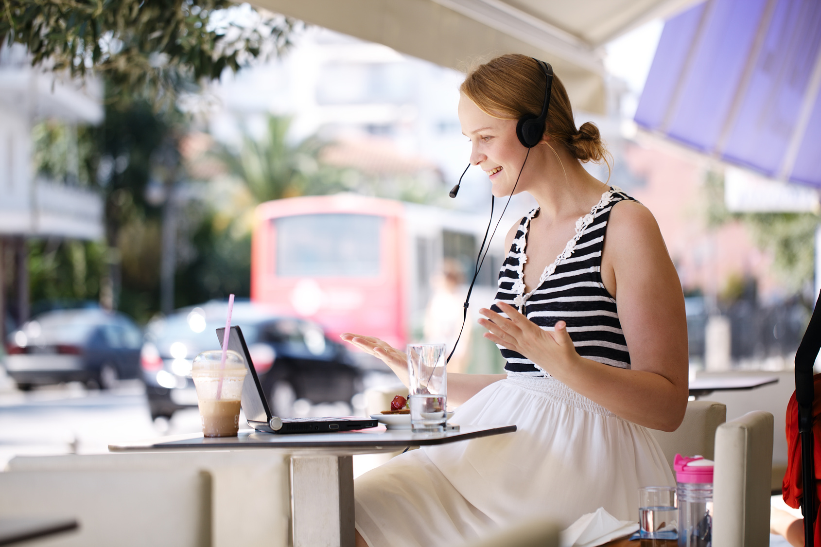 travel agent working at a cafe enjoying outdoors computer headset iced latte become a travel agent